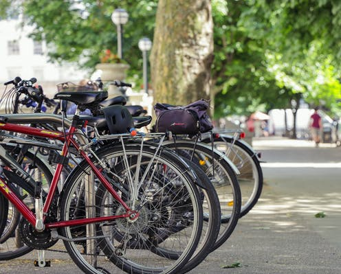 A row of parked bikes on a tree-lined British street.