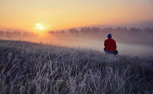 Man watching sunrise in nature during winter.