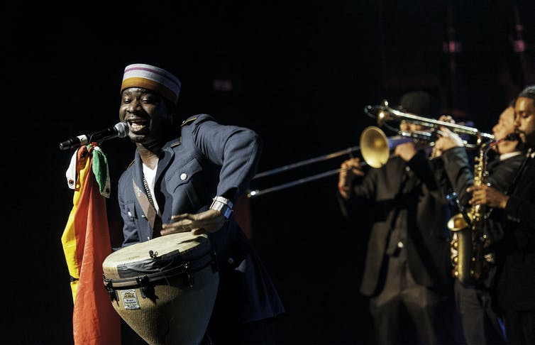 A man plays African drums and sings into a microphone, behind him a row of trumpeters and saxophonists.