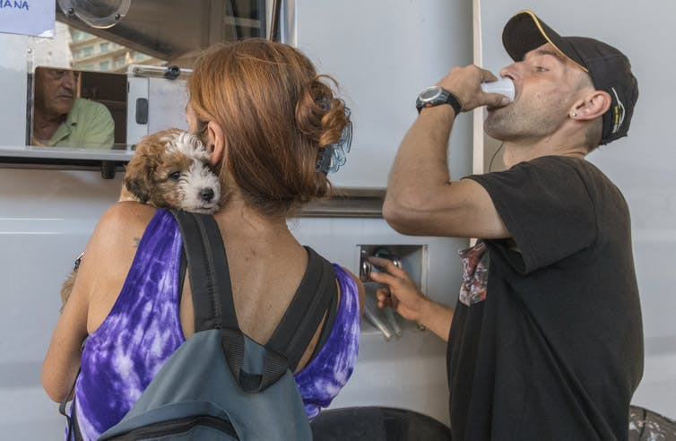 Woman with a dog waits at a white van while a man drinks from a tiny cup