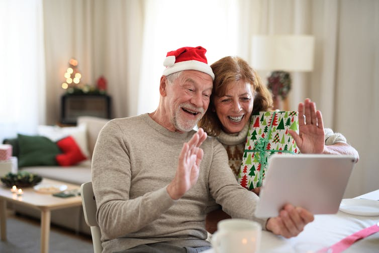 Older couple having a zoom chat at Christmas.