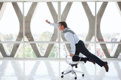 Un hombre de negocios atraviesa una sala vacía sobre una silla con ruedas imitando a Supermán.