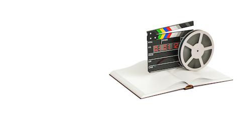 Claqueta electrónica, bobina de película sobre libro abierto.