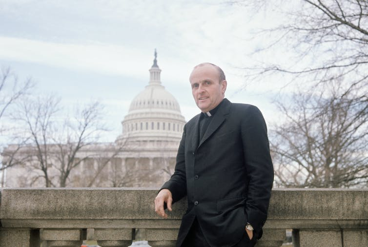 Rep. Robert Drinan, wearing his clerical collar, poses in front of the U.S. Capitol.
