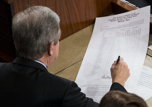 A man signs a piece of paper