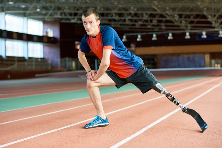 Man in sportswear at running track with prosthetic blade.