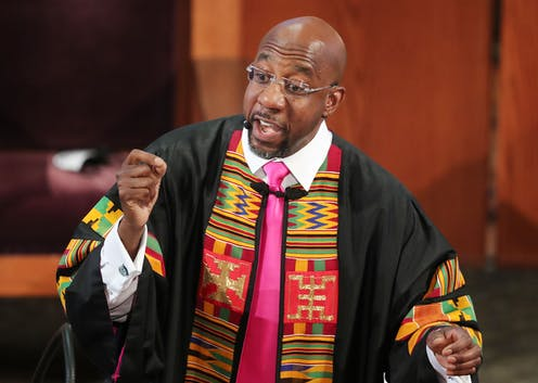Raphael Warnock, wearing a stole, gestures during a sermon.