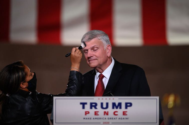 A woman brushes makeup on Franklin Graham's forehead as he stands at a podium during the 2020 Republican National Convention.