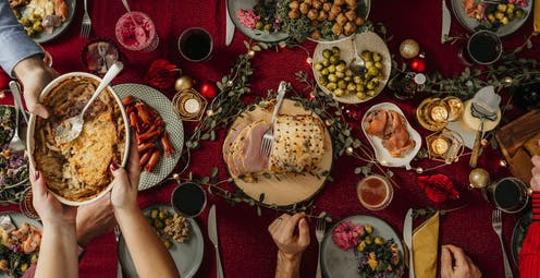 Someone passes a dish filled with food to someone else amid a table that displays many types of holiday foods.