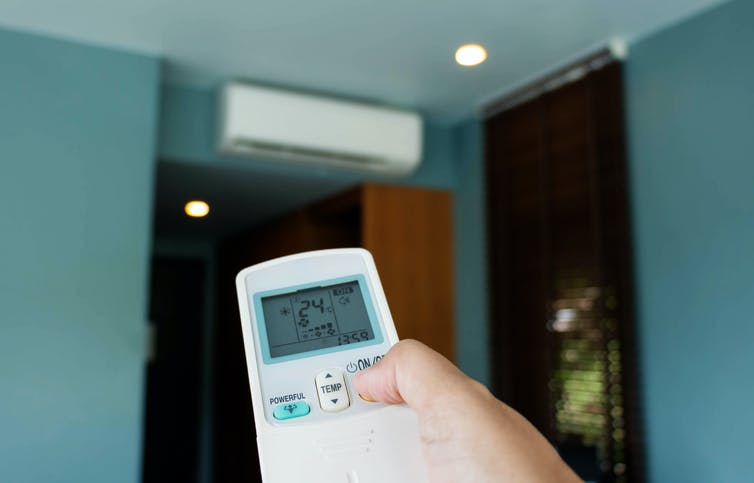 A person using a remote for their air conditioner