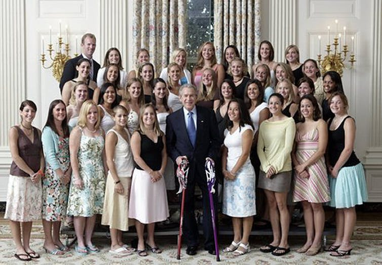 Group of young women meet the US President Bush, some are wearing thongs with formal dresses.