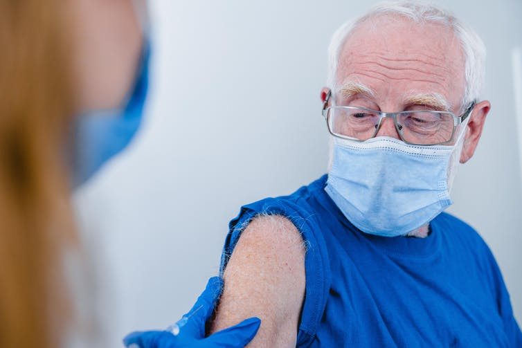 An older man wearing a mask has his sleeve rolled up in preparation for a vaccination.