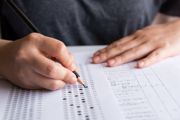 Student filling out multiple-choice answer form.