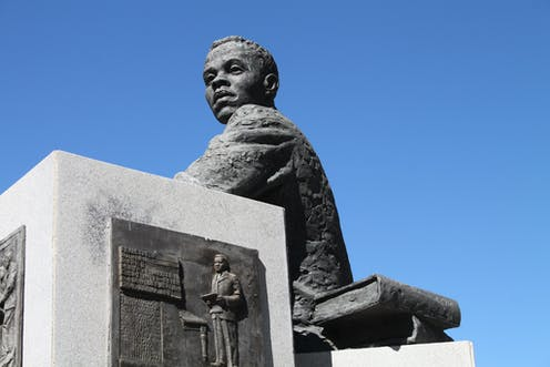 A sculpture of a young man in a jacket, seated with a book next to him. He's gazing towards the horizon, blue sky behind him.