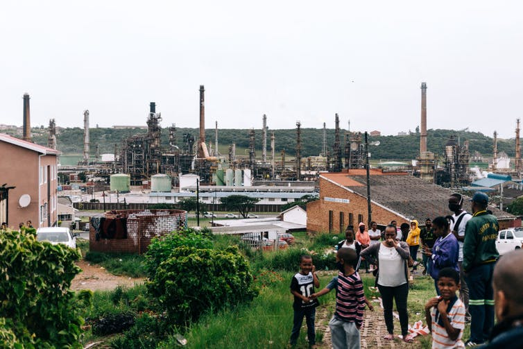 A crowd of people, including children, gathered near an oil refinery, which is located in a residential area.