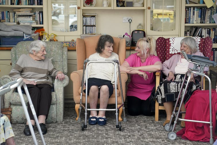 A care worker and residents talking in a care home
