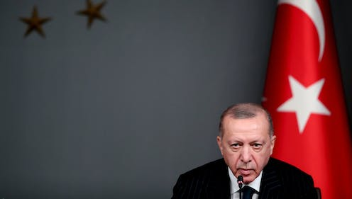 Turkish president Recep Tayyip Erdogan sits in front of a Turkish flag during a press conference  in Istanbul, October 2020