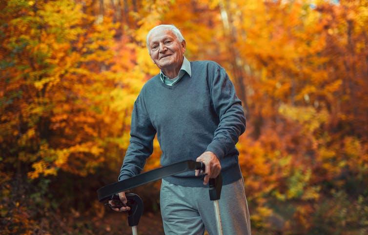Elderly man with walker out walking in a beech wood in autumn.