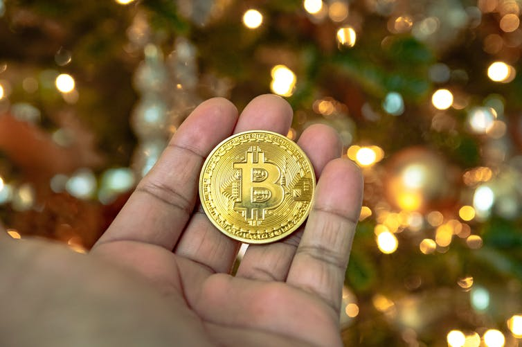 A person holds a gold bitcoin coin in front of a Christmas tree