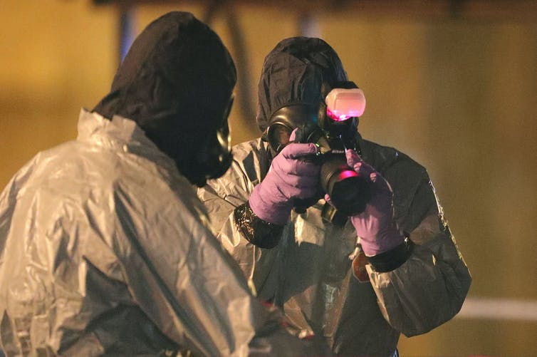 Two police investigators with protective clothing.