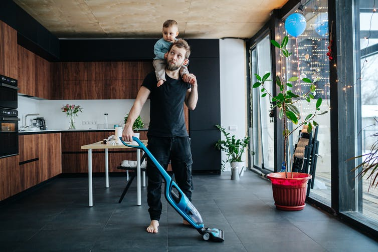 A dad vacuums with a toddler on his shoulders.