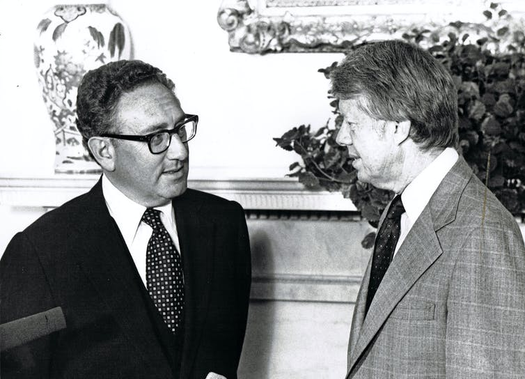 Former US Secretary of State Henry Kissinger (left) and President Jimmy Carter talk in the White House's Oval Office, Washington DC, August 15, 1977