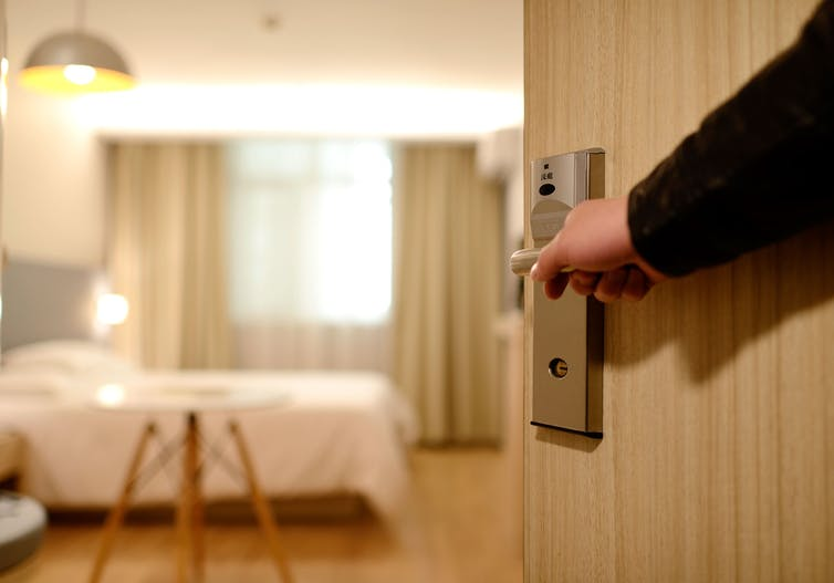 A porter opens the door into a brightly lit hotel room.