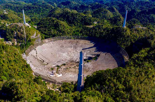An arial view of an enormous crumbling telescope dish surrounded by hilly terrain.