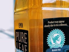 A bottle of iced tea with the Rainforest Alliance logo.