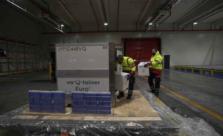Workers handling a shipment of vaccines in a large cold storage container.