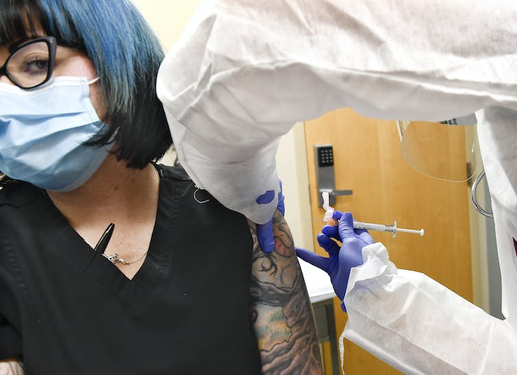 A healthcare worker receiving a COVID-19 vaccine.