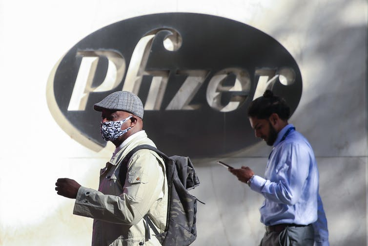 Two men in front of Pfizer headquarters in New York City.