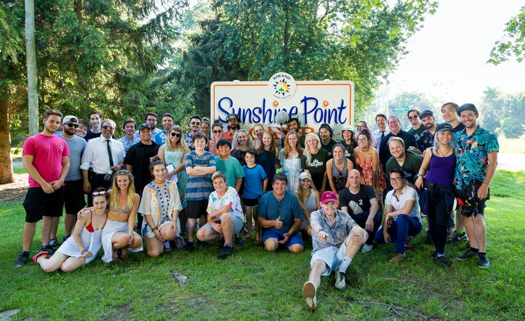 (A crowd outside in front of 'Sunshine Point' sign.