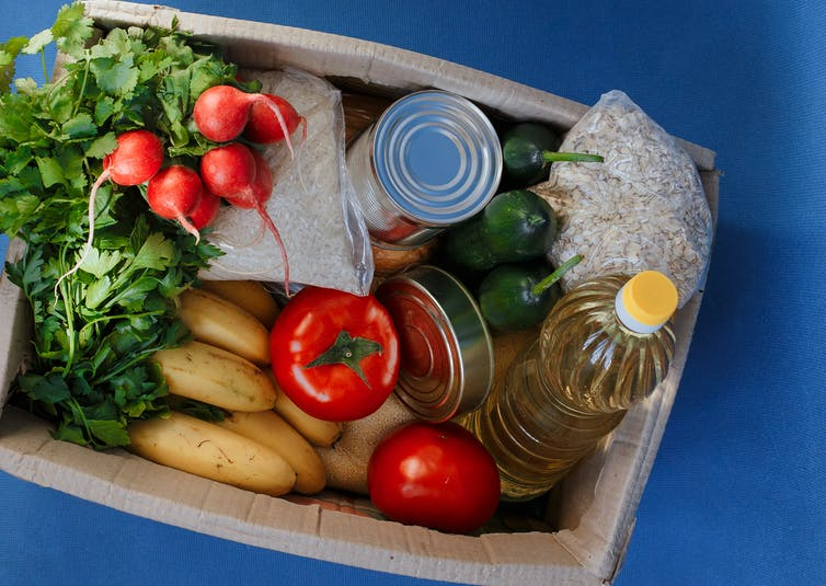 Box filled with fresh vegetables, canned goods and cooking oil