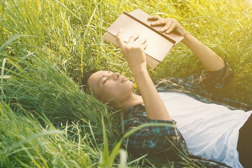 Young adult boy lying on the grass reading.
