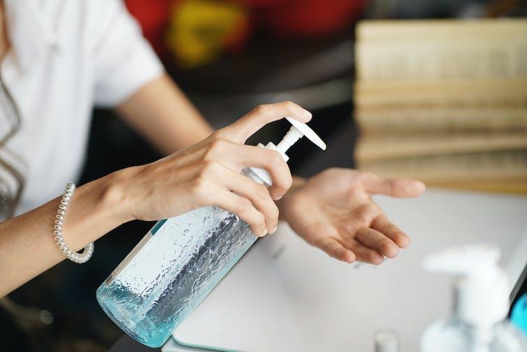 A woman uses hand sanitiser.