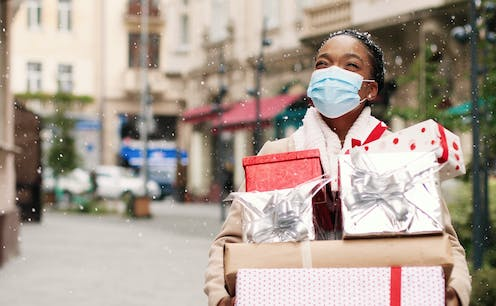 A woman stands in the snow on a high street smiling under a COVID mask holding presents