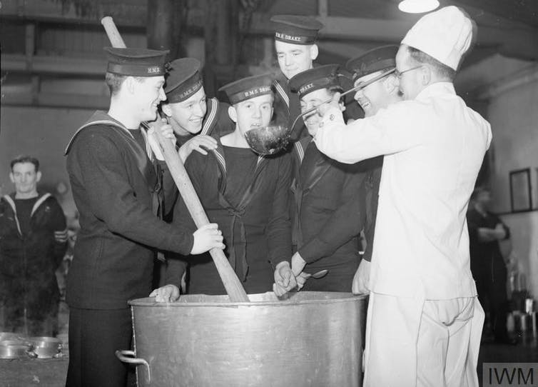 A group of sailors in uniform stirring a large cooking pot with a chef.