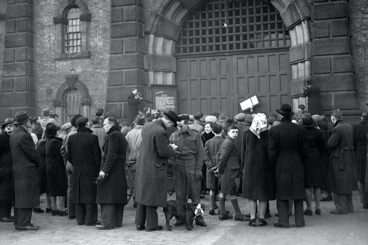 Group of people crowding in front of the gates of Wandsworth Prison in London in 1946.