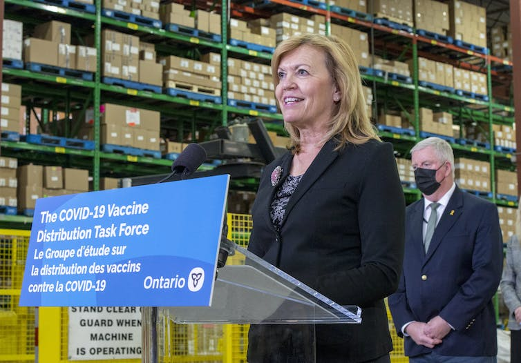 Christine Elliott stands at a podium with sign reading THE COVID-19 DISTRIBUTION TASK FORCE