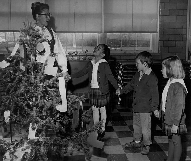 A teacher and students celebrate Christmas around a tree in school in this black-and-white photo from 1964