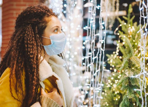 A woman in a face mask looking at a Christmas tree and Christmas lights