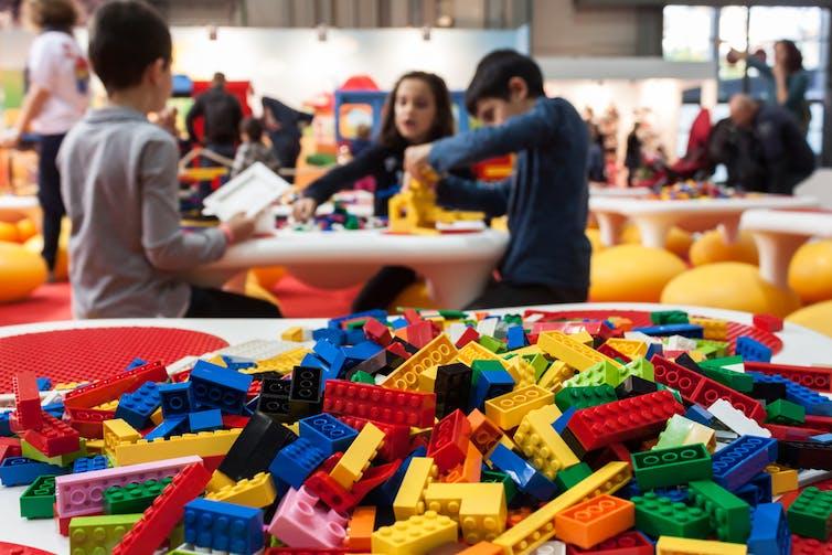 Un montón de ladrillos de Lego en primer plano con niños jugando con ellos en el fondo.