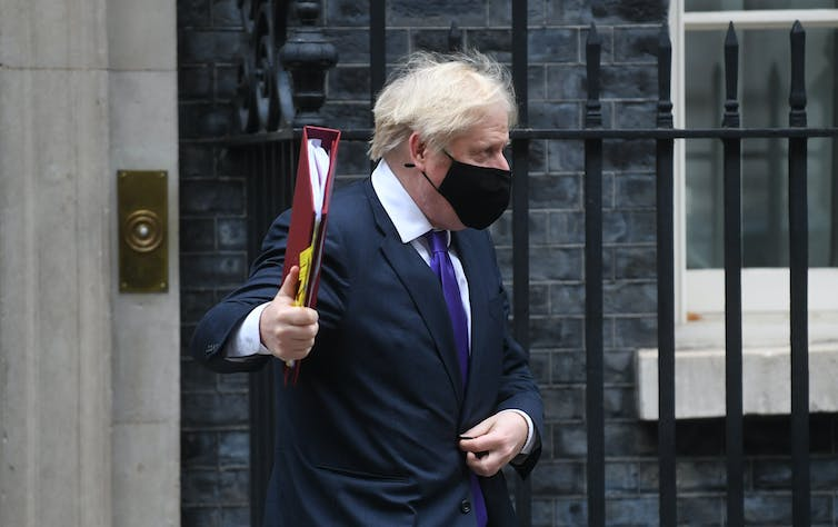 Prime Minister Boris Johnson leaving number 10 Downing Street, wearing a black mask.