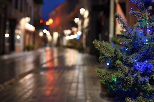 árbol de navidad con bolas azules en una calle desierta.