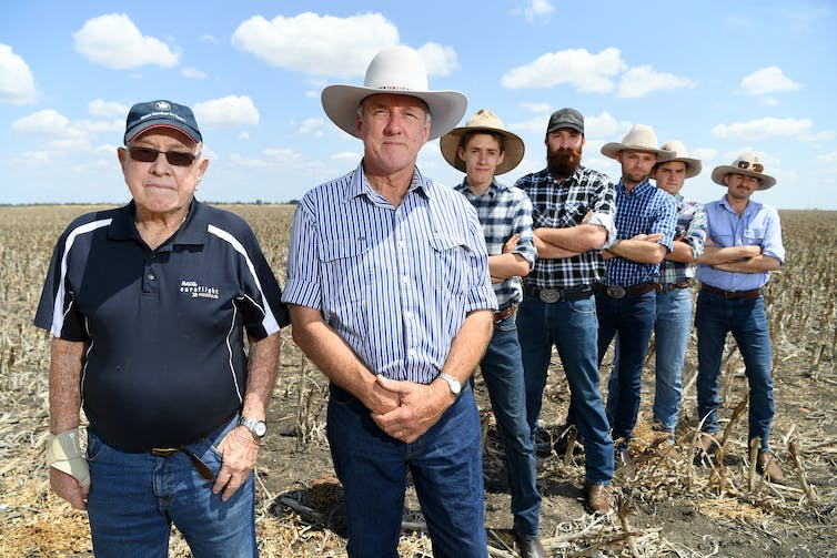 Three generations of a farmers stand on their land