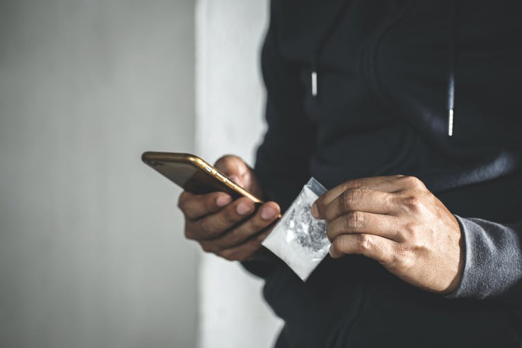 A man holds a small packet with white powder in one hand, and his phone in the other hand.
