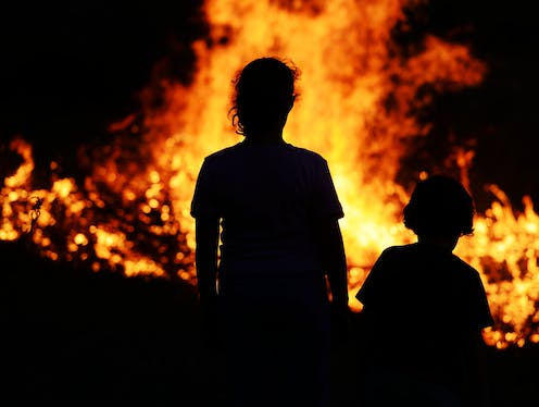 Woman and child standing in front of bushfire