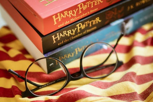 A pile of three Harry Potter books with a pair of reading glasses on a red and yellow striped cloth