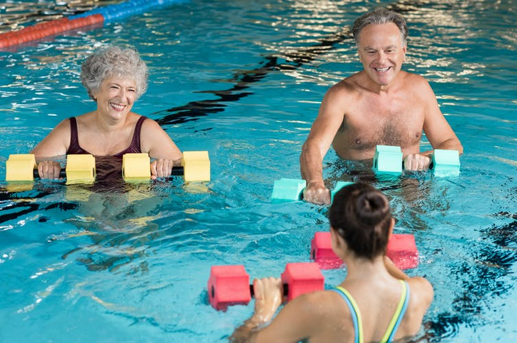 Older couple smile while performing water aerobics with a trainer.